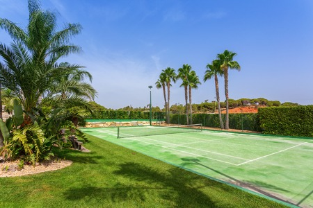 Tennis court in the garden with palm trees in Portugal. Stok Fotoğraf