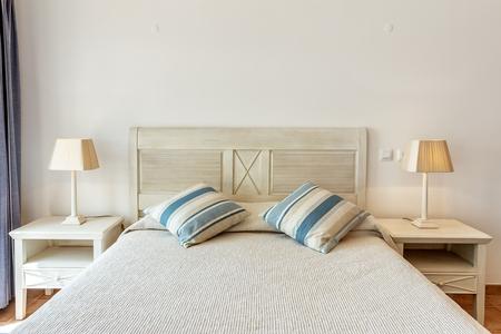 Dormitorio de estilo moderno con cama y almohadas. Vista frontal Foto de archivo