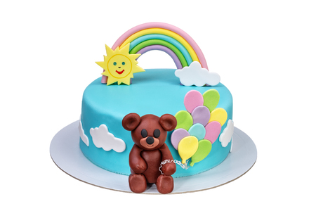 Cake for a childrens holiday with a bear balls and a rainbow.