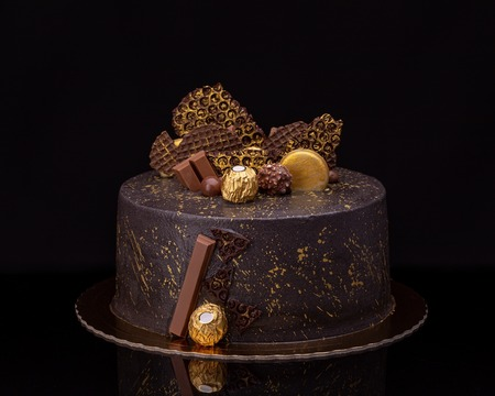 Delicious chocolate cake with candies on a black background.