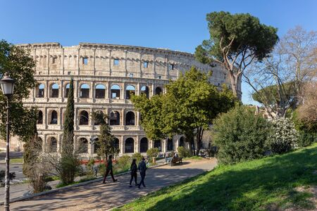 Tourists walk in the park overlooking the Colosseum in Rome Imagens