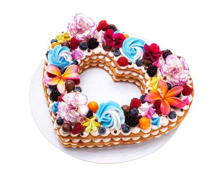 Heart shaped puff cake with fruit and flowers. Imagens