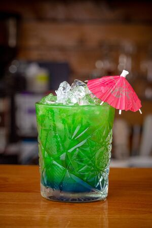 Green mint tonic cocktail, with ice on a bar