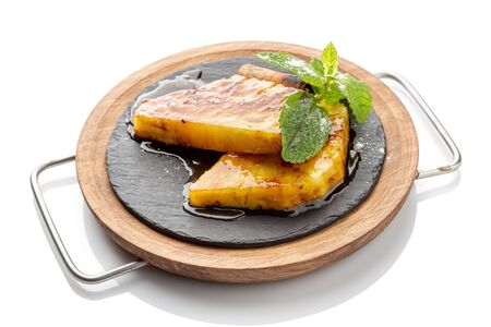 Pieces of pineapple with mint, poured with caramel for dessert.