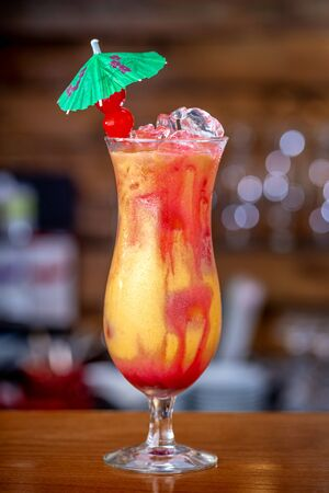 Glass of Passion fruit, pineapple, and pomegranate Cocktail.