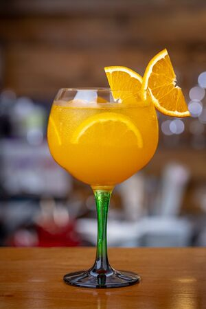 Orange tonic cocktail, with ice on a bar