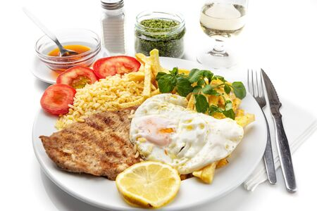 Dish for lunch of fried meat, pork chop with egg, potatoes. Portuguese dish. Imagens