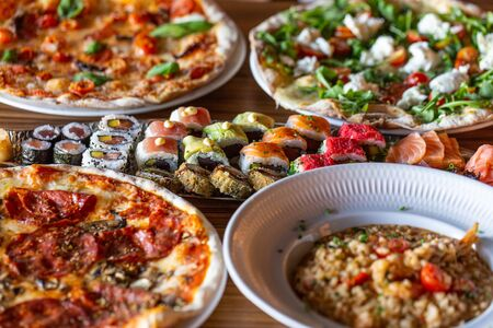 A variety of food on the table in a restaurant made of pizza, sushi. Close-up