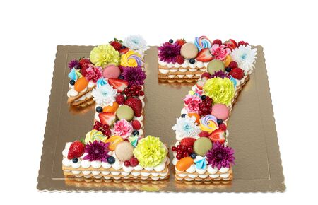 A cake in the shape of a figure sixteen of flowers and fruits.