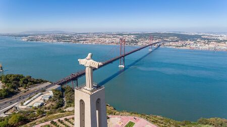 Aerial. Panorama from sky with a drone, a bridge on April 25 and a statue of Jesus Christ. Lisbon Portugal. Imagens