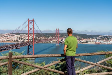 A male tourist contemplates a view of the bridge on April 25 in Lisbon. Banco de Imagens