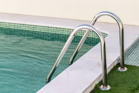 Inox railings in the pool on the grass.