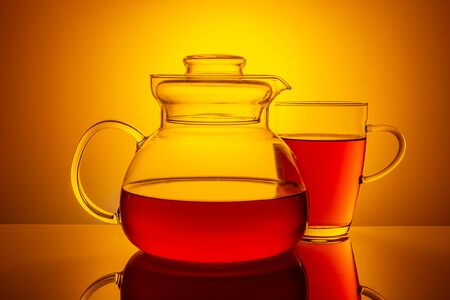 Glass teapot with a filled glass, on a yellow gradienton dark background