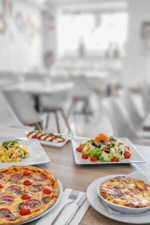 A group of Italian dishes in the restaurant for lunch. Pizza, lasagne, salad, feta. Restaurant in the background. Vertical photo