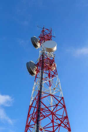 A modern tower antenna for broadcasting telephone, television, and Internet signals. Against the sky