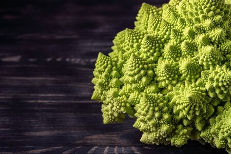 Romanesco broccoli on a dark wooden background. For vegans and a healthy diet. Copy space