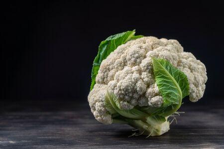 Cauliflower on a wooden dark background, closeup. For vegetarianism. Copy space. Banco de Imagens