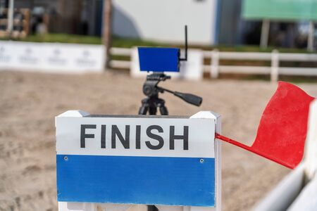A device with a red flag for registering the finish line in equestrian racing at the racetrack.