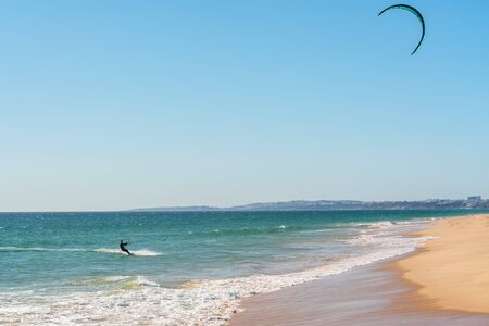 The athlete practices kate board surfing the sea on the waves. Summer in Portugal Algarve