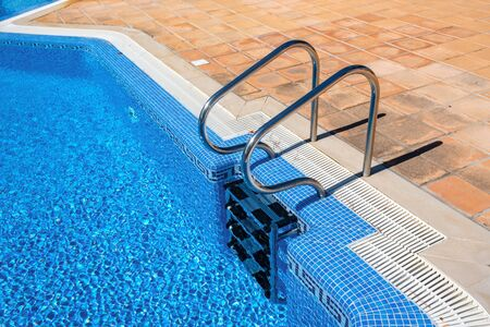 Summer image of pool detail, handrails and clear water for tourism. Stock fotó