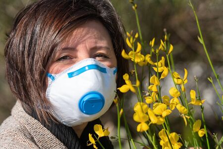 A woman in a mask on her face, to protect against spring allergies and from coronavirus.