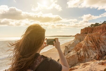 A girl on the coast of the Atlantic Ocean of Portugal, photographs seascapes, the beaches of the Algarve, Falesia. Warm toning