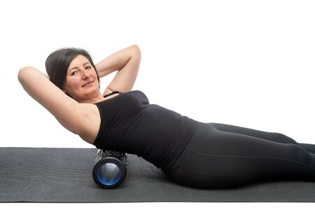 A middle-aged woman with saggy skin on a gymnastic mat with myofascial roller does an exercise on her back on a white background.