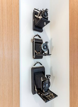 Vintage cameras with a black, leather case hanging in a corner on a white wall.