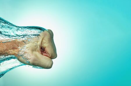 Man hit the water, the concept of strength and self-confidence, assertiveness and success. Close up on a blue background