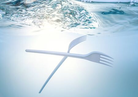 The global ecological problem, environmental pollution, waste in the seas and rivers. Plastic fork under water.