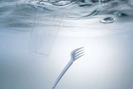 The global environmental problem, environmental pollution, waste in the seas and rivers. Plastic cup and fork, under water. Фото со стока