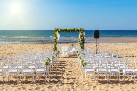 Romantic view and flower decorations on the beach near the sea, for a wedding ceremony with flowers. Europe, Portugal, against backdrop of bright sun.