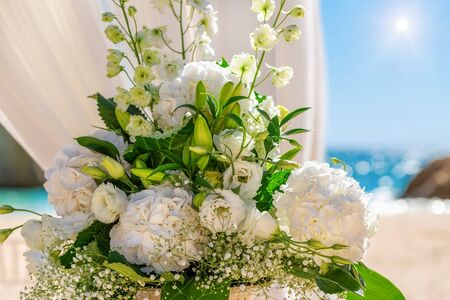 Beautiful wedding bouquet of the bride on a background of a sunny day and the beach.