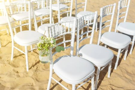 Wedding ceremony on the beach on a sunny day. A set of white chairs for guests decorated with flowers. 免版税图像