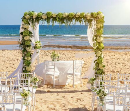 Romantic wedding ceremony on the ocean, beach on a sunny day. A wooden arch decorated with fresh flowers. White armchairs in the sand.