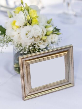 Bridal bouquet standing in a glass near an old, golden photo frame. Copy space.