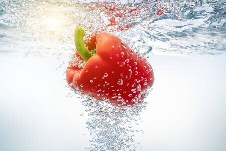 Falling red bell peppers in ecologically clean water through which the sun breaks through. Close-up.