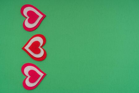 Vertical red hearts on a green background. Copy space.