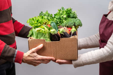 Man getting handed a basket of produce from a woman. Both of them are wearing masks. High quality photo