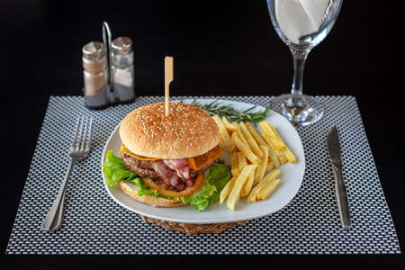Beef hamburger meal with potato chips on the side, on a white plate and a black background. Quality fast-food. High quality photo