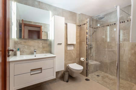 Beige colored bathroom interior, a shower with a glass door and a ceramic toilet, also a few towels on the walls. High quality photo