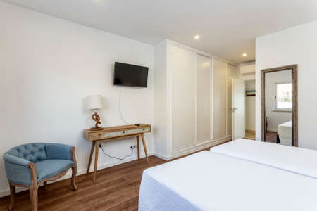 Clean and simple looking bedroom with a double bed facing a TV, small table stand and chair.