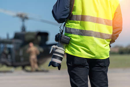 A military photographer, a reporter, in a signal yellow vest, ready to work in front of a military helicopter. Close-up. The background is blurred. High quality photo