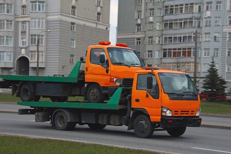 tow truck carrying a broken tow truck on a city street Stok Fotoğraf