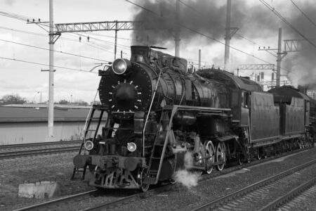 Black and white retro steam train in clouds of smoke rides by rail, rolling tourists