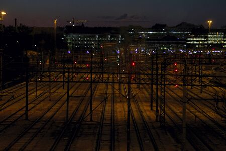 Deserted railway tracks with traffic lights at night at a large railway station