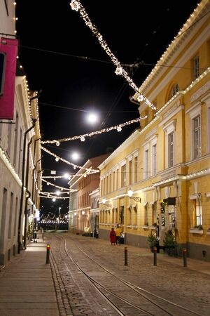 Evening city street decorated with electric garlands for Christmas