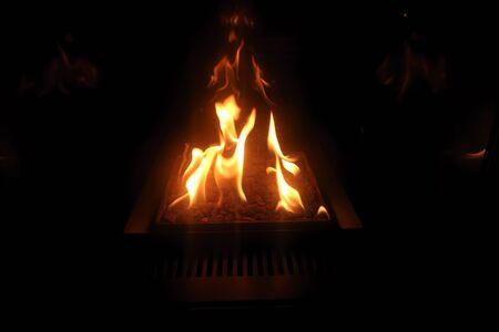 des flammes dansant sur des charbons dans l'obscurité de la nuit Banque d'images