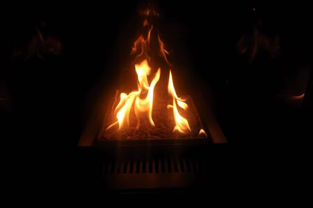 llamas bailando sobre brasas en la oscuridad de la noche Foto de archivo