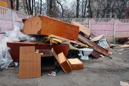 Old furniture dumped in a pile in the trash and white toilet
